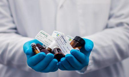 man in scrubs holding medicines pills