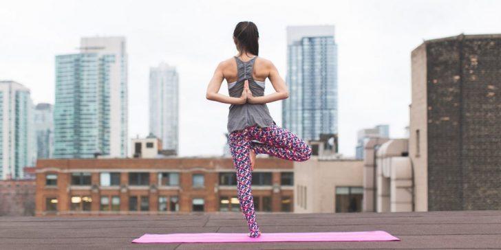 woman-standing-on-pink-yoga-mat-meditating